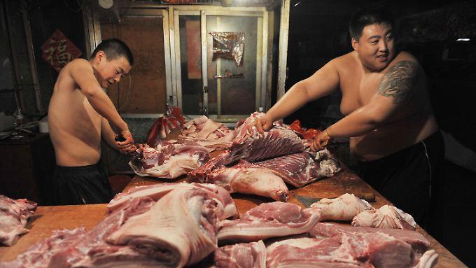 Ohne Arbeitshemd und Schutzhandschuhe: Fleischer zerlegen ein Schwein in einem Markt im chinesischen Shenyang.