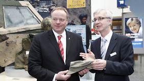 Dietmar Preißler nimmt die Mütze aus den Händen des Ministers entgegen.