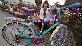 Petra Schulz präsentiert das bestrickte Fahrrad vor der bestrickten Bank.