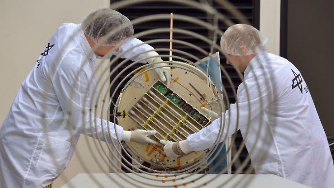 Raumfahrtingenieure arbeiten im Reinraum des DLR in Bremen am AI-Satellit.