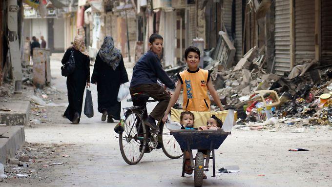 In Deir al-Zor kutschiert dieser Junge seine Brüder in einer Schubkarre durch die zerstörte Stadt.