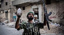 Ein Kämpfer der Freien Syrischen Armee hält seine Maschinenpistole und ein abgefeuertes Artilleriegeschoss der Regierungstruppen in den Händen.