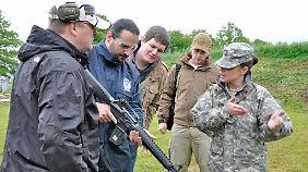 Eine US-Soldatin zeigt örtlichen Schützen ihr Arbeitsgerät.