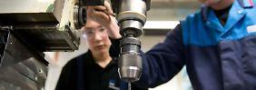 Auszubildene lernen im BMW-Motorradwerk in Berlin den Umgang mit einer Bohrmaschine.