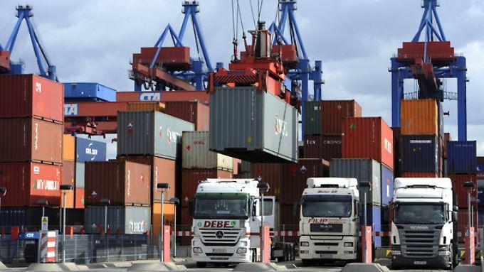 Im Hamburger Hafen werden LKW mit Containern beladen.