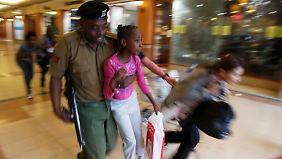 Ein Soldat bringt zwei Mädchen in Sicherheit.