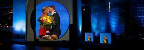 Bundestagswahl 2013: An der Spree wirft ein leistungsstarker Beamer Live-Bilder einer glücklichen Wahlsiegerin an die Fassade des Marie-Elisabeth-Lüders-Hauses.