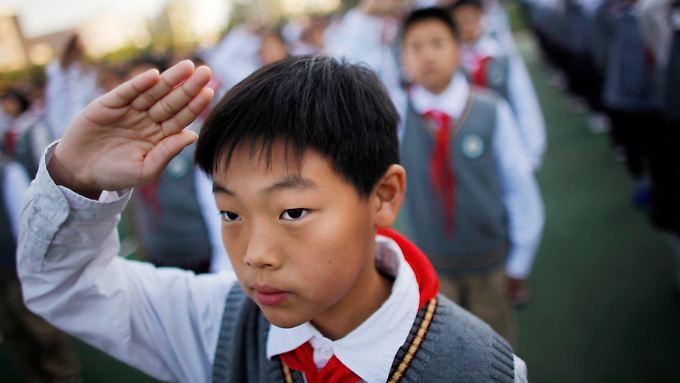 An einer Schule in Shanghai zeigt ein Schüler den Pioniergruß.