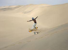 """""""Sandboarder"""" in den Wüstendünen bei Walvis Bay."""