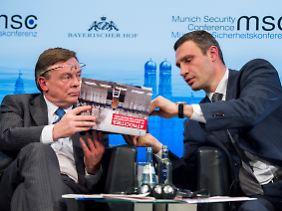 Vitali Klitschko (rechts) zeigt dem ukrainischen Außenminister Leonid Koschara Fotos vom Maidan. Koschara tut zumindest interessiert.