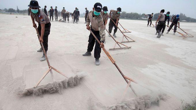 Polizeibeamte befreien die Start- und Landebahnen von Asche.