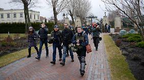 Journalisten werden von Regierungsgegnern durch die Residenz des Präsidenten in einem Vorort von Kiew geführt.