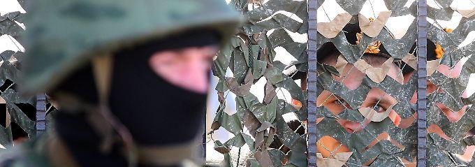 """Nach russischer Darstellung ist dieser Soldat, der vor dem Hauptquartier der ukrainischen Marine postiert ist, ein Mitglied der """"Selbstverteidigungskräfte"""" der Krim."""