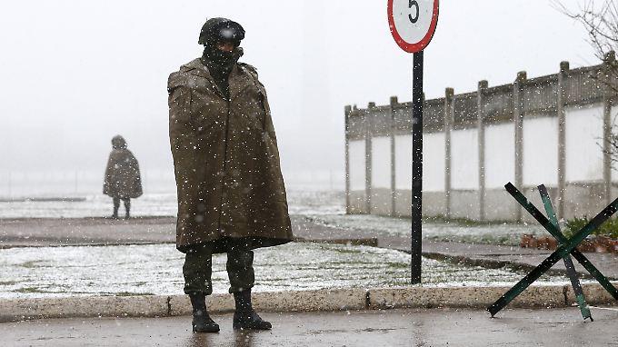 Vor einer Militärbasis in der Ukraine stehen bewaffnete Kräfte. Vermutlich handelt es sich um Russen.