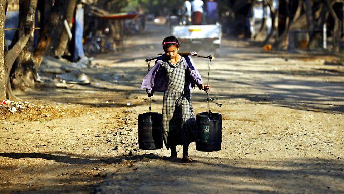 Wasser holendes Mädchen in Myanmar: Viele Millionen Menschen weltweit haben weder Zugang zu Trinkwasser noch zu Strom.