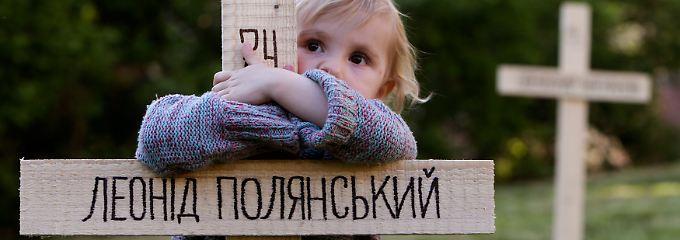 Ein Kind umarmt in Prag eines der  Holzkreuze für die Todesopfer auf dem Maidan. Bei den Protesten in Kiew waren im Februar mehr als 100 Menschen gestorben.