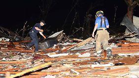 Einsatzkräfte steigen durch Trümmerberge in Louisville im US-Bundesstaat Mississipi.
