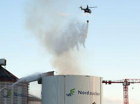Das beschädigte Silo im Abendlicht: Dach und Zufuhrbrücke sind eingestürzt, vom Hubschrauber lässt die Feuerwehr Wasser auf die schwelenden Zuckermassen abwerfen.