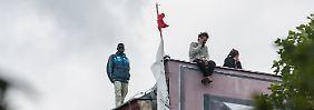 Immer wieder zeigen sich auf dem Dach der Schule die Flüchtlinge mit ihren deutschen Unterstützern.