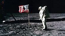 Buzz Aldrin steht neben der Fahne der USA, die er auf dem Mond gehisst hat.