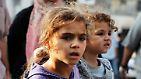 Kleine Kinder tragen ihre noch kleineren Geschwister aus der Gefahrenzone.