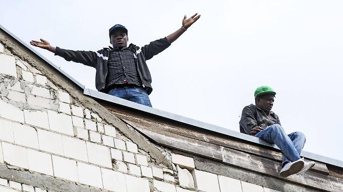 Verstehen die Welt nicht mehr: Zwei Flüchtlinge auf dem Dach des ehemaligen Hostels.