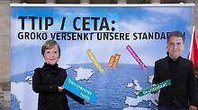 Mehrere Oppositionsparteien und Organisationen protestierten in dieser Woche gegen die geplanten Abkommen TTIP und Ceta. Hier tragen Aktivisten Masken von Angela Merkel und Sigmar Gabriel.