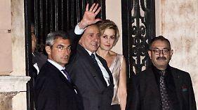 Silvio Berlusconi grüßt den heranfahrenden Wladimir Putin.