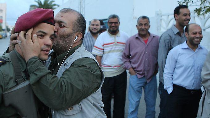 Hach, wie schön ist doch eine friedliche Wahl! Dieser Tunesier kann gar nicht mehr an sich halten und verpasst einem Soldaten einen Freudenkuss.