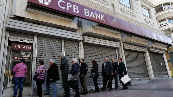 März 2013 - Bankkunden stehen Schlange vor einer geschlossenen Filiale der Cyprus Popular Bank in Athen.