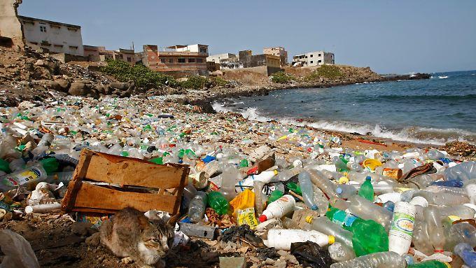 in Blick auf den Atlantikstrand von Ngor, Dakar, Senegal. Im Meer werden die Flaschen zu kleinsten Teilchen zerrieben.