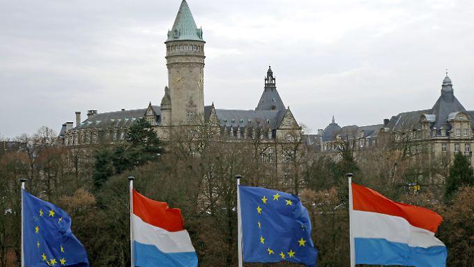 Luxemburgische und europäische Fahnen wehen vor dem Turm der Staatssparkasse in der Stadt Luxemburg.