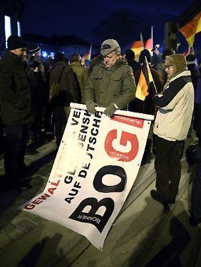 """Ein Bogida-Aktivist rollt sein Banner zusammen. Außerhalb Dresdens konnte die """"Bewegung"""" nicht Fuß fassen."""