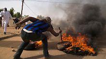 """Ein Mann verbrennt bei Protesten gegen """"Charlie Hebdo"""" in Niger einen Reifen."""