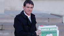 """Frankreichs Premier Valls mit der aktuellen Ausgabe von """"Charlie Hebdo""""."""