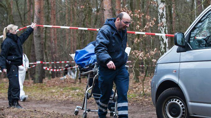 Mitarbeiter der Gerichtsmedizin transportieren die Leiche ab.
