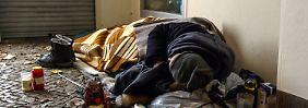 Ein Obdachloser liegt in einem Berliner Hauseingang.