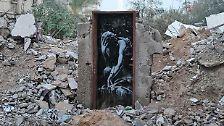 """Der Graffiti-Künstler macht mit seinen Werken (hier """"Bomb damage"""") auf die Probleme in der Krisenregion aufmerksam, aber auch ..."""