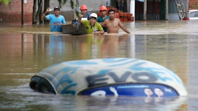 Diese Männer waten über die vom Fluss Acre überschwemmte Straße an der brasilianisch-bolivianischen Grenze.