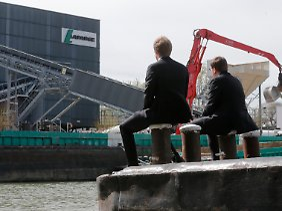 Fusionen und Übernahmen verändern Vieles: In einem Binnenhafen bei Paris beobachten Geschäftsleute das Treiben bei Lafarge.