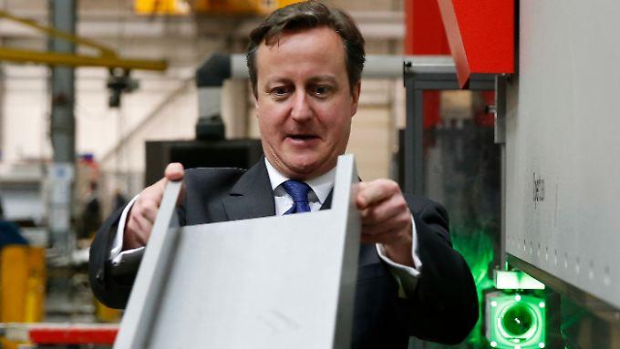 David Cameron begutachtet während einer Fabrikbesichtigung  ein Metallwerkstück.