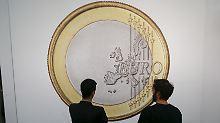 """Stärkeres Wachstum im Zentrum der Eurozone? Zwei Kunstexperten vor dem Werk """"SUPERFLEX, Euro 2012"""", einem der Ausstellungsstücke der am Donnerstag anlaufenden Art Cologne 2015 in Köln."""