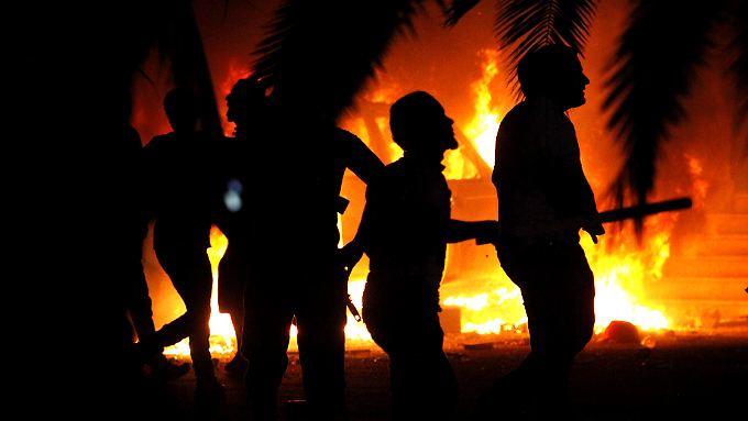 Bengazi: Einwohner schauen auf ein brennendes Gebäude, das Kämpfer von Ansar al-Scharia besetzt hatten. Aus der Gruppe ging zum Teil der libysche IS hervor.