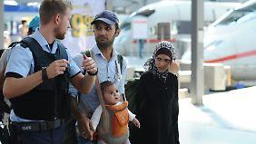 Ein Polizist begleitet eine Familie aus Syrien durch den Bahnhof.