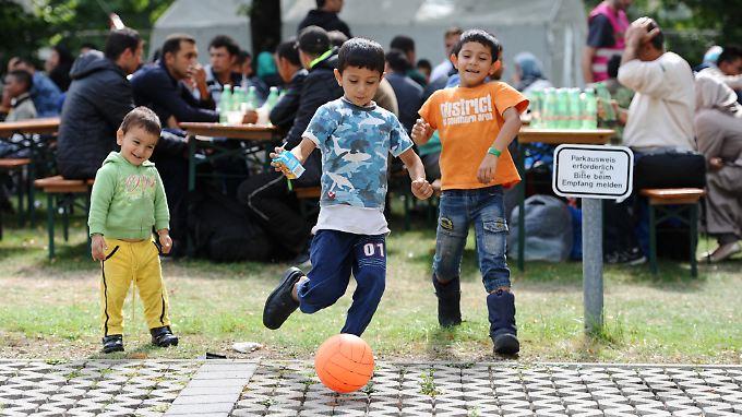 Tausende Flüchtlingskinder werden eine Betreuung brauchen. Hier spielen drei von ihnen vor einem Zeltlager in München.