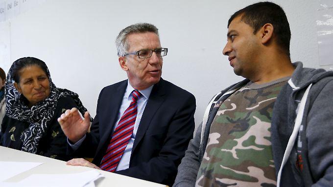 Innenminister de Maizière mit Flüchtlingen im niedersächsischen Friedland