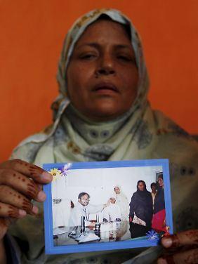 Eine Iranerin zeigt ein Foto ihres Mannes, der immer noch als vermisst gilt.