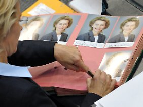 Arbeitsministerin von der Leyen unterschreibt derweil Autogrammkarten.