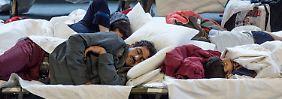 Auf Feldbetten schlafen die Flüchtlinge in der August-Schärttner-Halle in Hanau (Hessen).