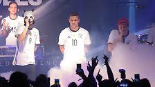 ... präsentierten Weltmeister Lukas Podolski sowie seine Nationalmannschafts-Kollegen ...
